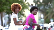 Black woman and adult daughter walking down city street
