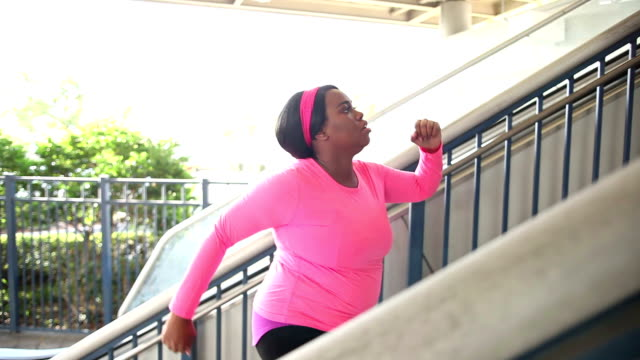 Black woman exercising in city, power walking up stairs