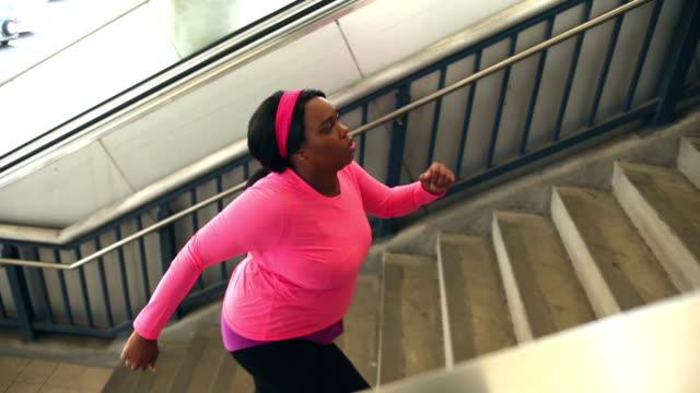 Schwarze Frau, die in der Stadt, macht Treppensteigen Ausübung