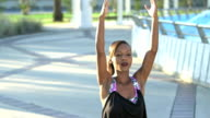 Black woman in city doing yoga fountain