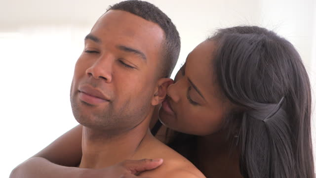 Black woman nibbling on boyfriend's ear