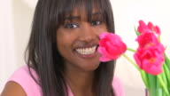 Black woman smiling with bouquet of flowers