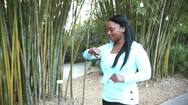 Schwarze Frau mit Fitness Tracker Schritte zählen