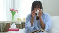 Black woman with cold blowing nose into tissue