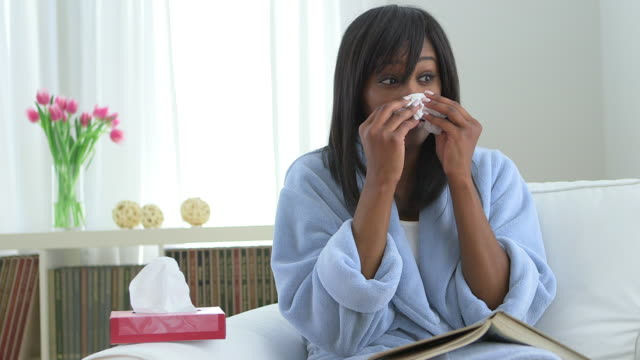 Black woman with flu, blowing nose into tissue