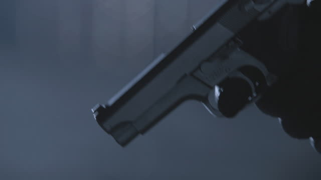 CU Black-gloved hand firing a gun towards the ground, gun lingers in the air after being fired