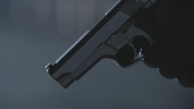 CU Black-gloved hand firing a gun towards the ground