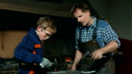 HD DOLLY: Blacksmith Assisting A Young Trainee
