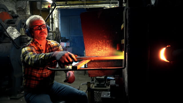 Blacksmith examining metal in furnace
