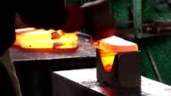 Schmied Lege ein anhaltender Bügeleisen im forge