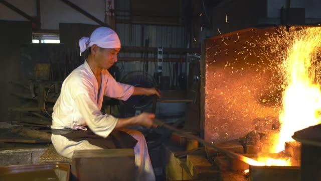 Schmied wütend Pumpen den Balg auf seinem Ofen