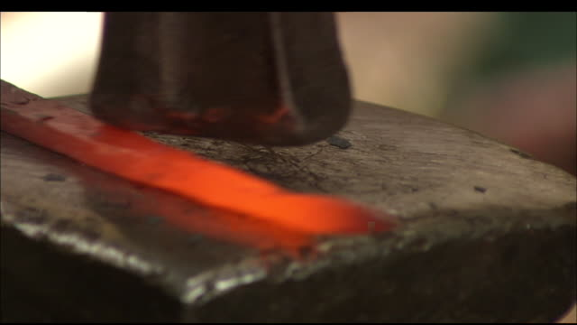 A blacksmith hammers a hot piece of metal. Available in HD.