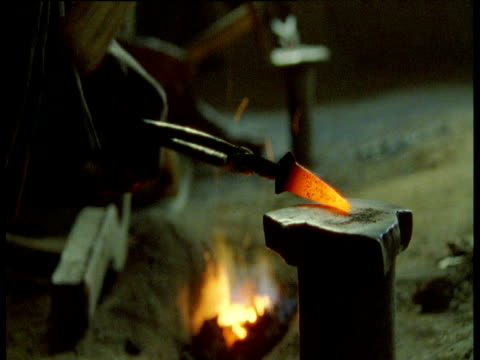 Blacksmith hammers metal in smithy, Djenne