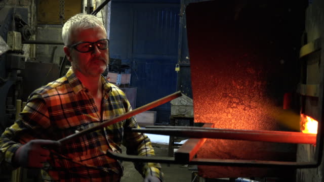 Blacksmith inserting metal to furnace
