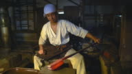 Blacksmith inspecting a block of beating metal