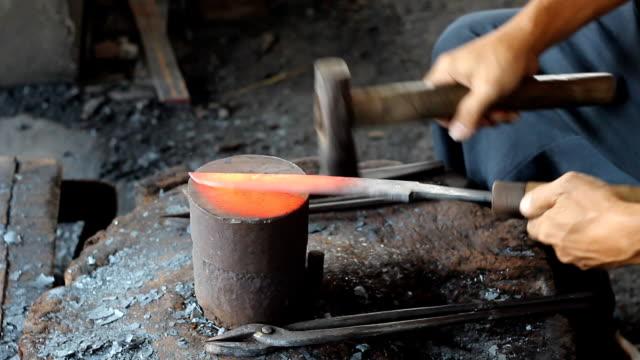 Blacksmith making knife.