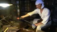 Blacksmith moulding a block of metal
