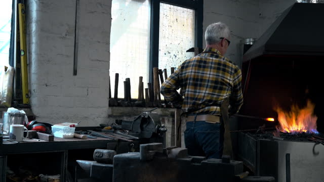 Blacksmith moving metal from furnace and using anvil