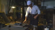 Blacksmith using hammer to shape metal