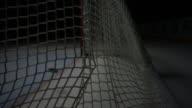 Blade of ice hockey stick hitting puck into goal hitting white net net rebounding amp coming to rest dark BG Slap shot sports score scoring shot on...