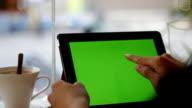 Vuoto tablet con schermo verde su primo piano con una mano