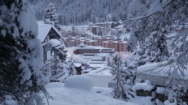 A blanket of snow covers the buildings and trees as the early morning light rises above the mountains in Davos Switzerland on Monday Jan 18 2016