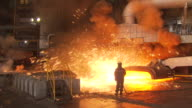 blast furnace with sparks and a worker