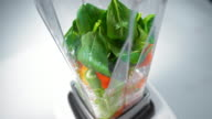 SLO MO Blender mixing vegetables for a green smoothie