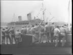 A blimp flies over The Queen Elizabeth liner at sea / view of the ship liner from the cockpit of a blimp / crowds of soldiers on ship deck / shot of...