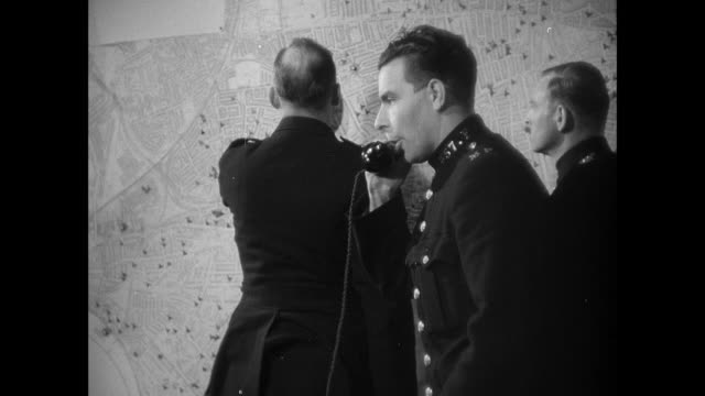 MONTAGE A blimp flying through the sky and a police superintendent reviewing bombing locations pinpointed on a map and then reporting the results to Scotland Yard / United Kingdom