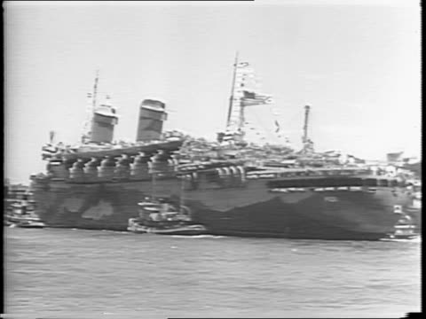 Blimp hovers over ship / Queen Mary ship arrives in NYC / Navy transport ship USS West Point carries thousands of soldiers / troops wave from...