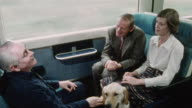 1978 HA Blind passenger on a train sitting with her guide dog and a deaf passenger as another passenger is using sign language to assist their conversation / United Kingdom