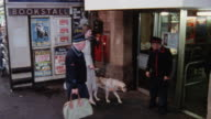 1978 MONTAGE Blind traveler with seeing eye dog entering train station and traveler in wheelchair being pushed by train conductor / United Kingdom