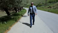 Blindfolded Businessman Walking on the Country Road