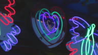 CU Blinking neon heart shaped sign on Love bugs ride in amusement park at night, Dallas, Texas, USA