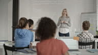 Blond female programmer explaining program code to school children