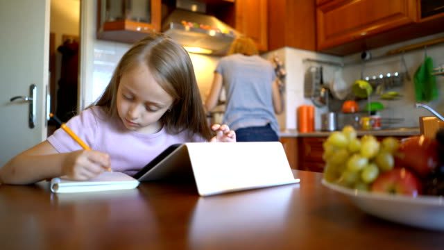 Blond girl browsing on the digital tablet and handwriting in her journal