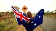 Blond girl holding Australian flag in air near Kangaroo sign