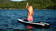 Blond girl paddleboarding