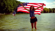 Blond girl waving American flag in the lake.