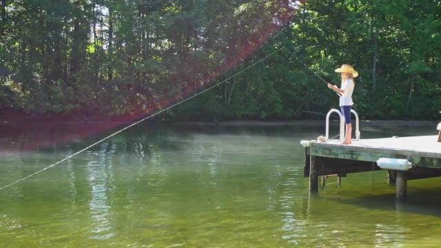 Blond meisje draagt een cowboyhoed vissen uit het Dock van een Misty Lake