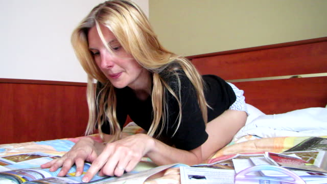 Blond woman on the bed, planning her vacation detination tour