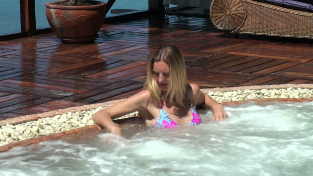 Blond woman relaxing in an outdoor whirlpool spa