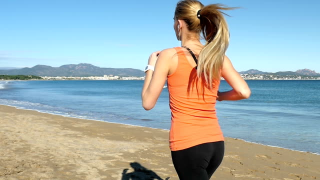 Blond woman running along the sea