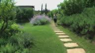 Blonden Frau zu Fuß in einer marvelous flowered toskanische Garten