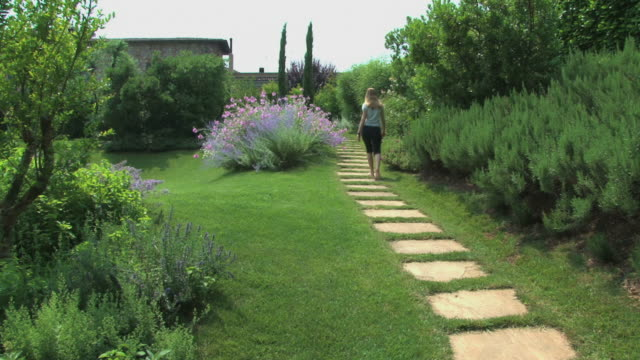 Blond woman walking in a marvelous flowered Tuscan garden