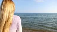 Blonde junge Frau, die mit Blick auf das Meer