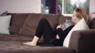 Blonde junge Frau vor dem Fernseher mit Bunny auf dem Schoß