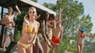 Blonde Frau kaukasischen in gelben Bikini tanzen mit ihren Freundinnen bei einer Pool-party