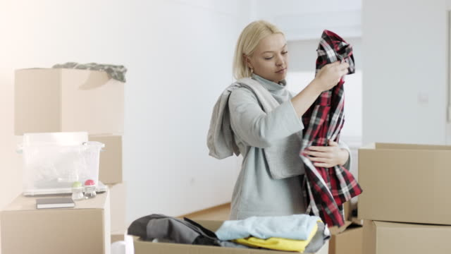 Blonde girl folding clothes in cardboard box